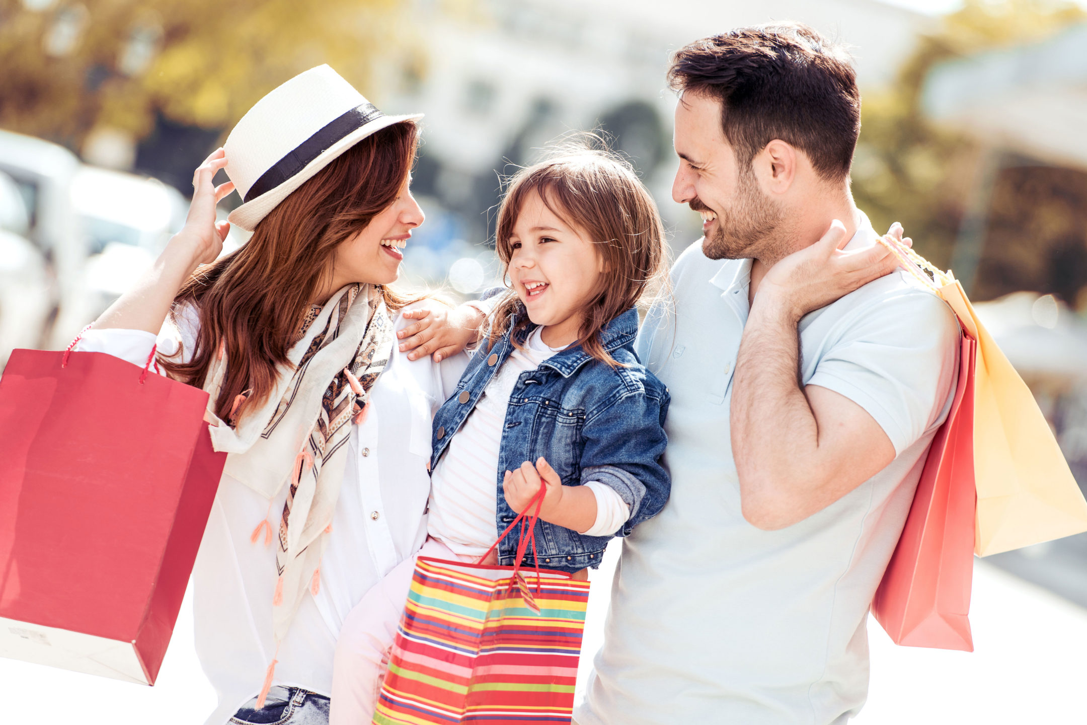 a young family smiling and shopping together with shopping bags