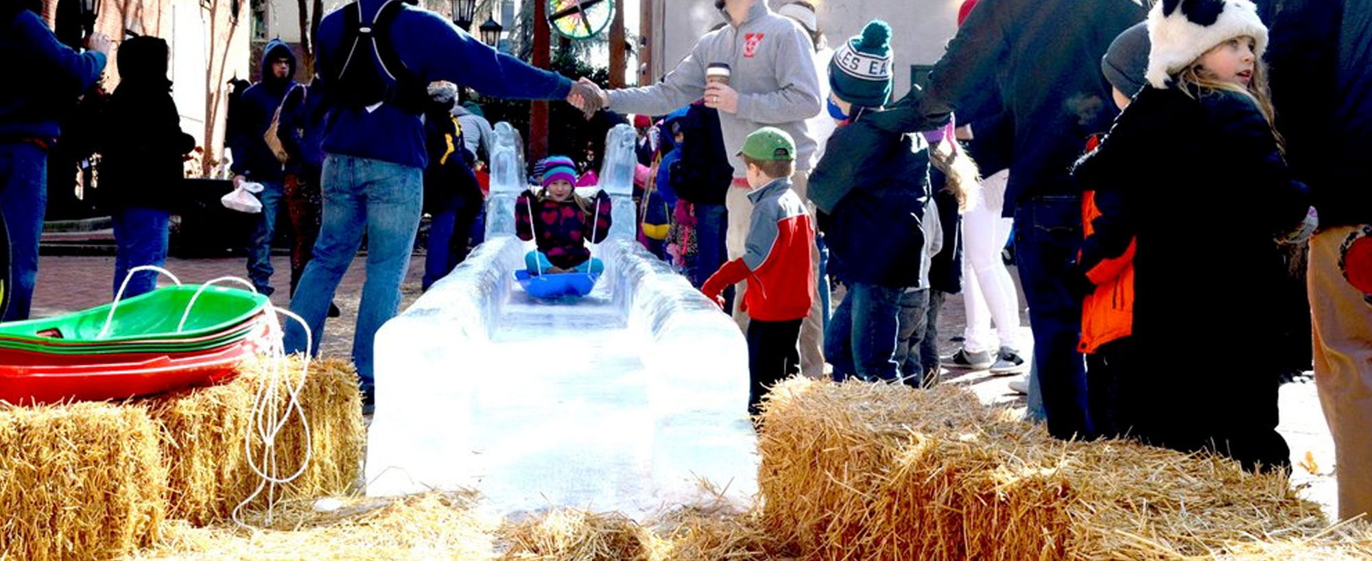 a young child sledding on an ice sculpture at a fun gathering