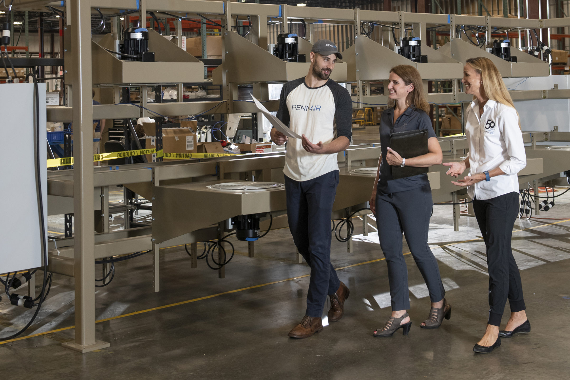 three people walking and discussing plans while in a warehouse/factory