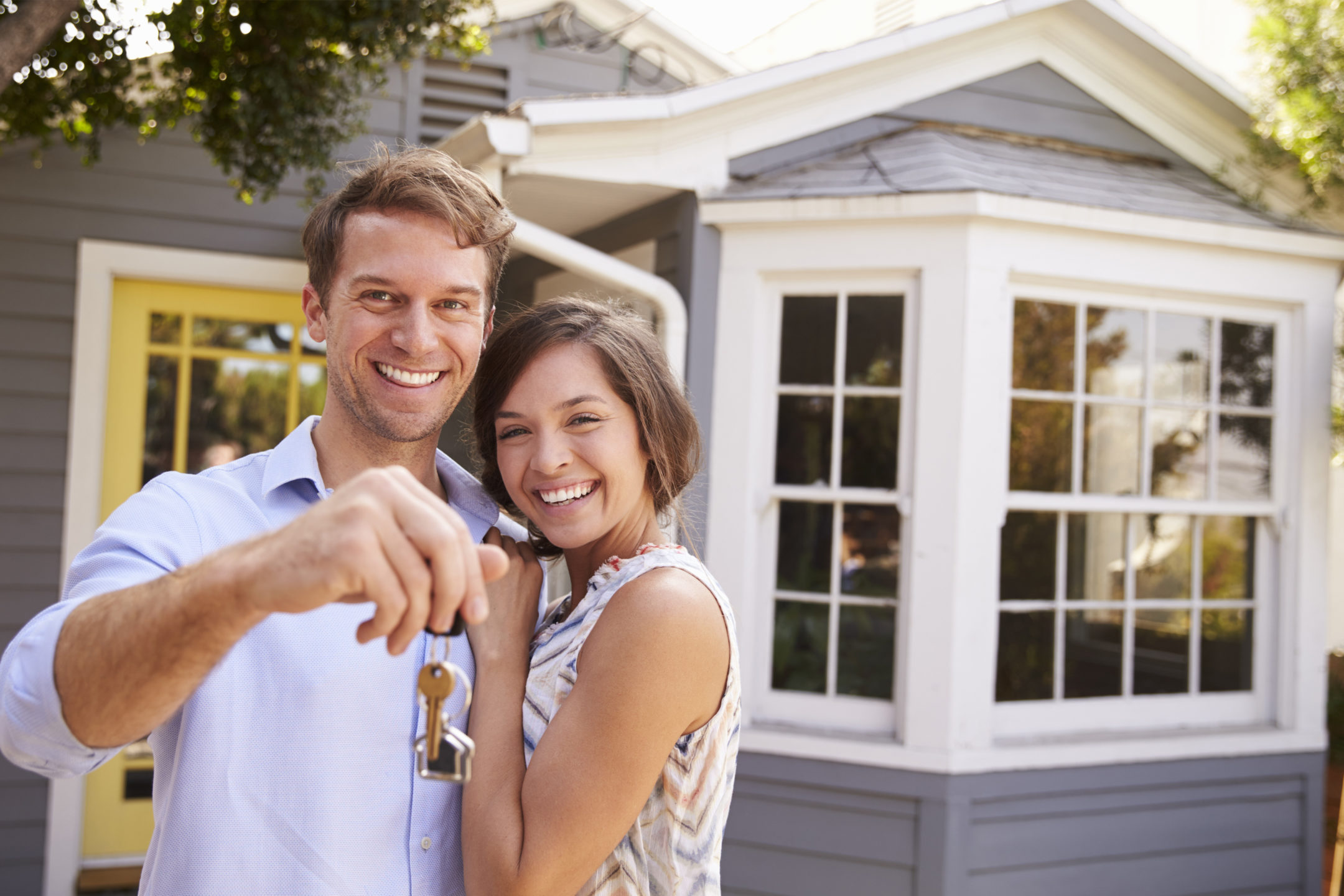a young couple smiling in front of a house and holding out house keys