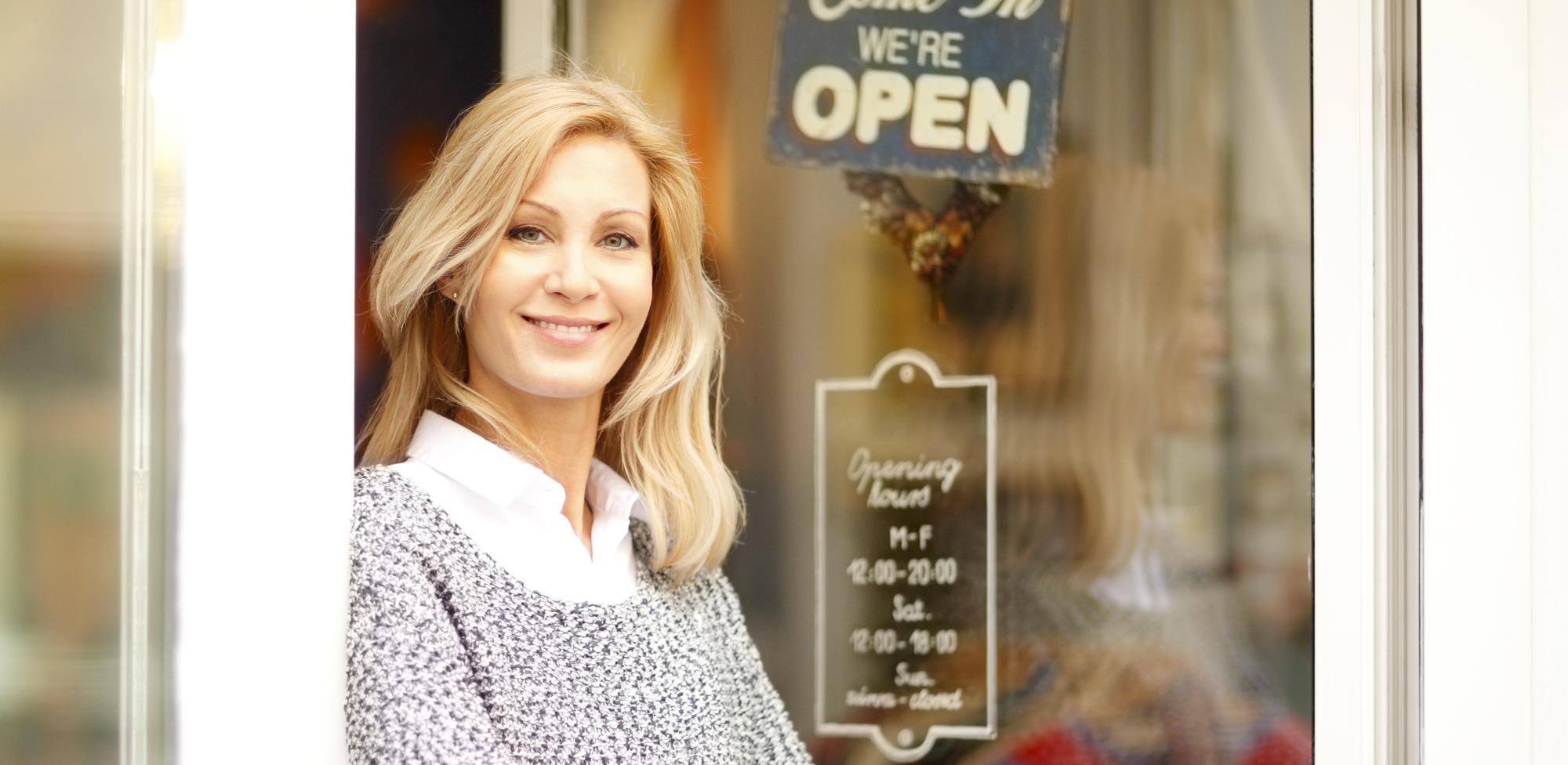 woman standing in front of business open sign on door