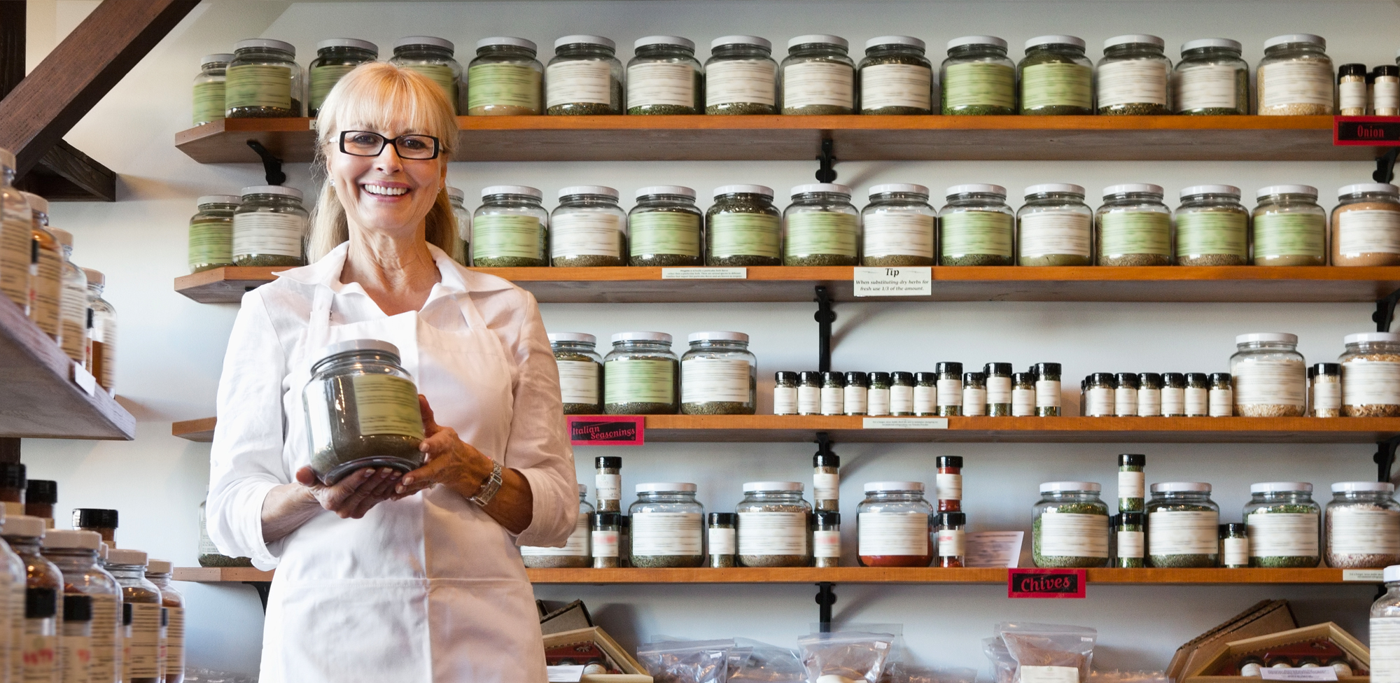 a business owner holding a glass jar in front of a wall filled with glass jars