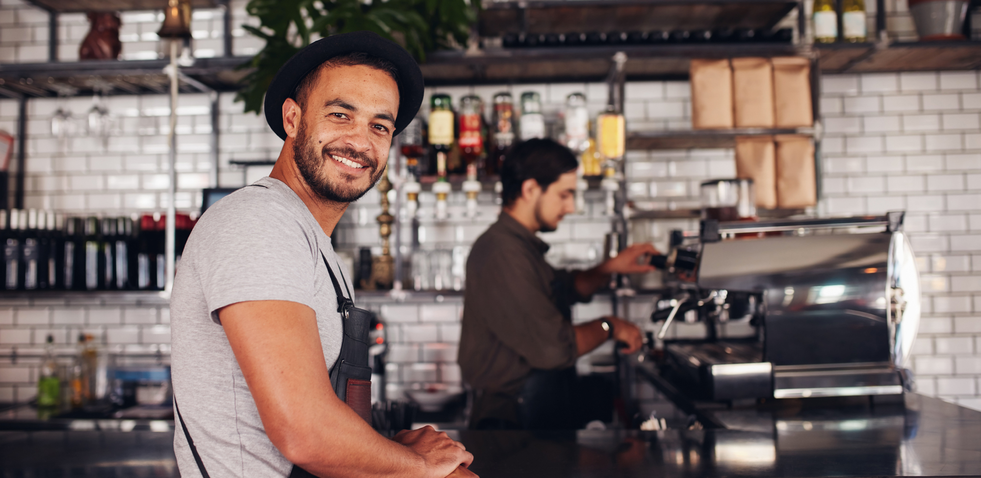 male barista at work and smiling at the camera