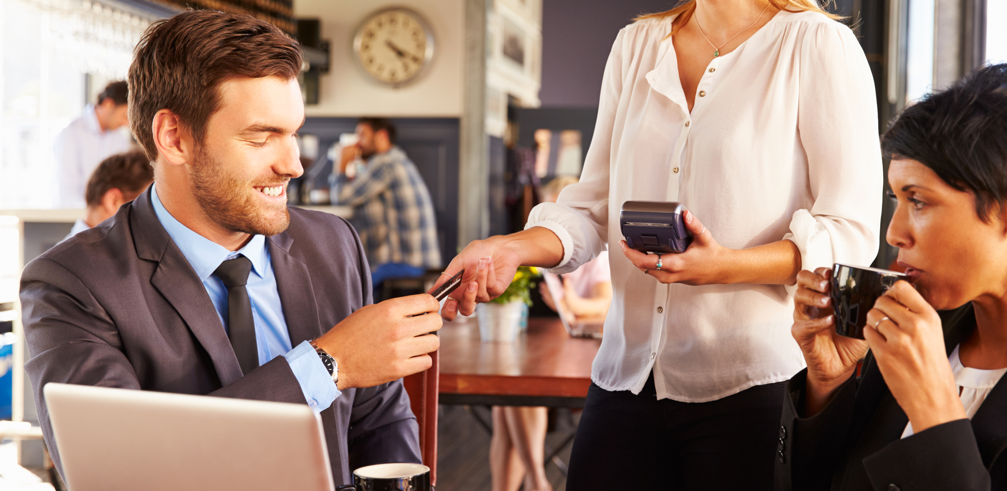 business man and woman in restaurant sitting at table and handing credit card to waitress