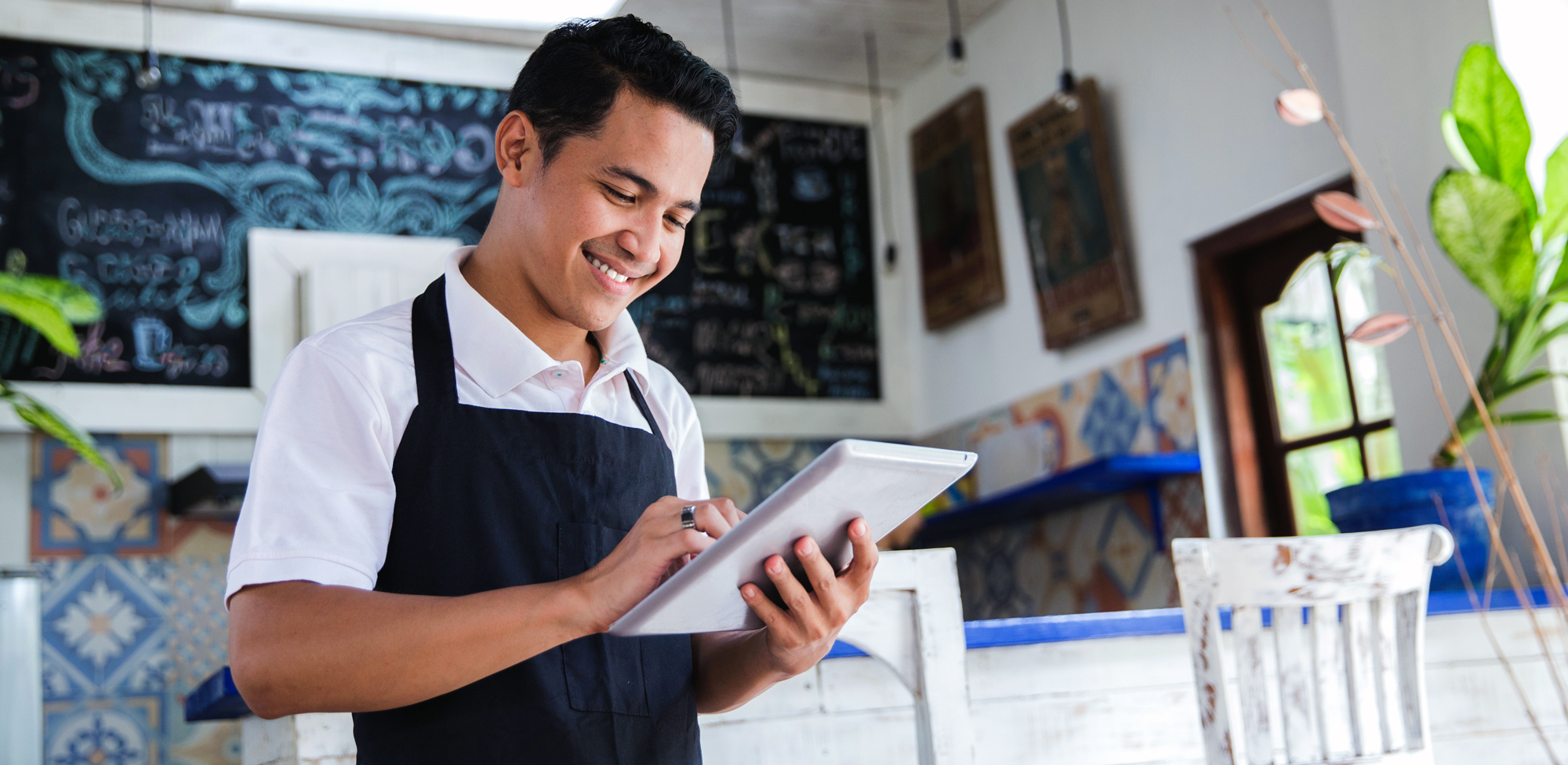 man in coffee shop on tablet