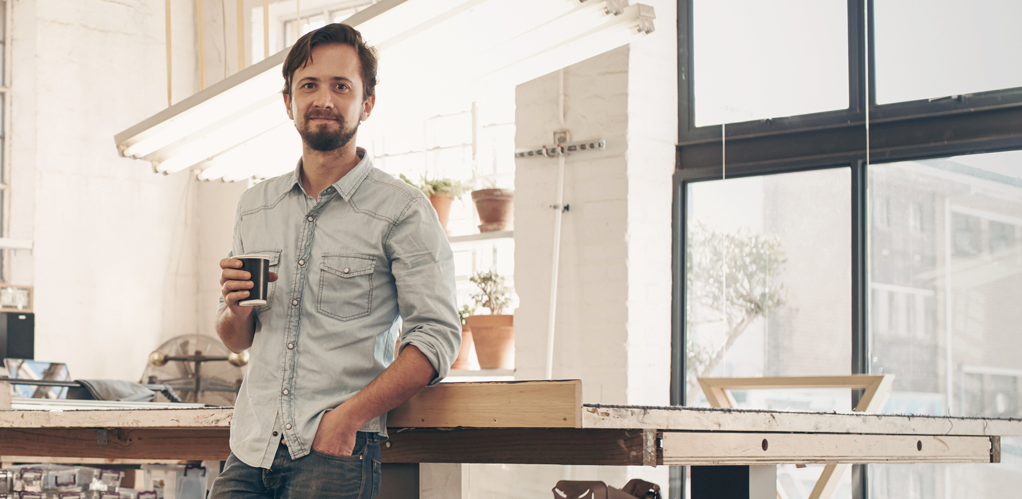 man inside kitchen holding coffee mug smiling