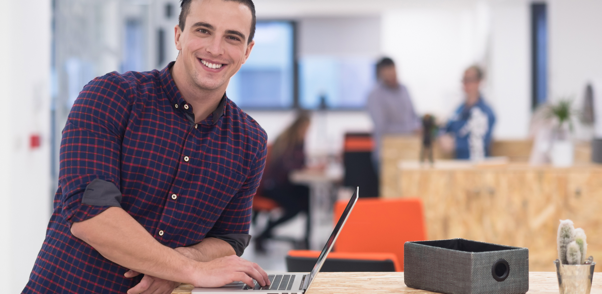 young man leaning on the table where his open laptop is and smiling at the camera