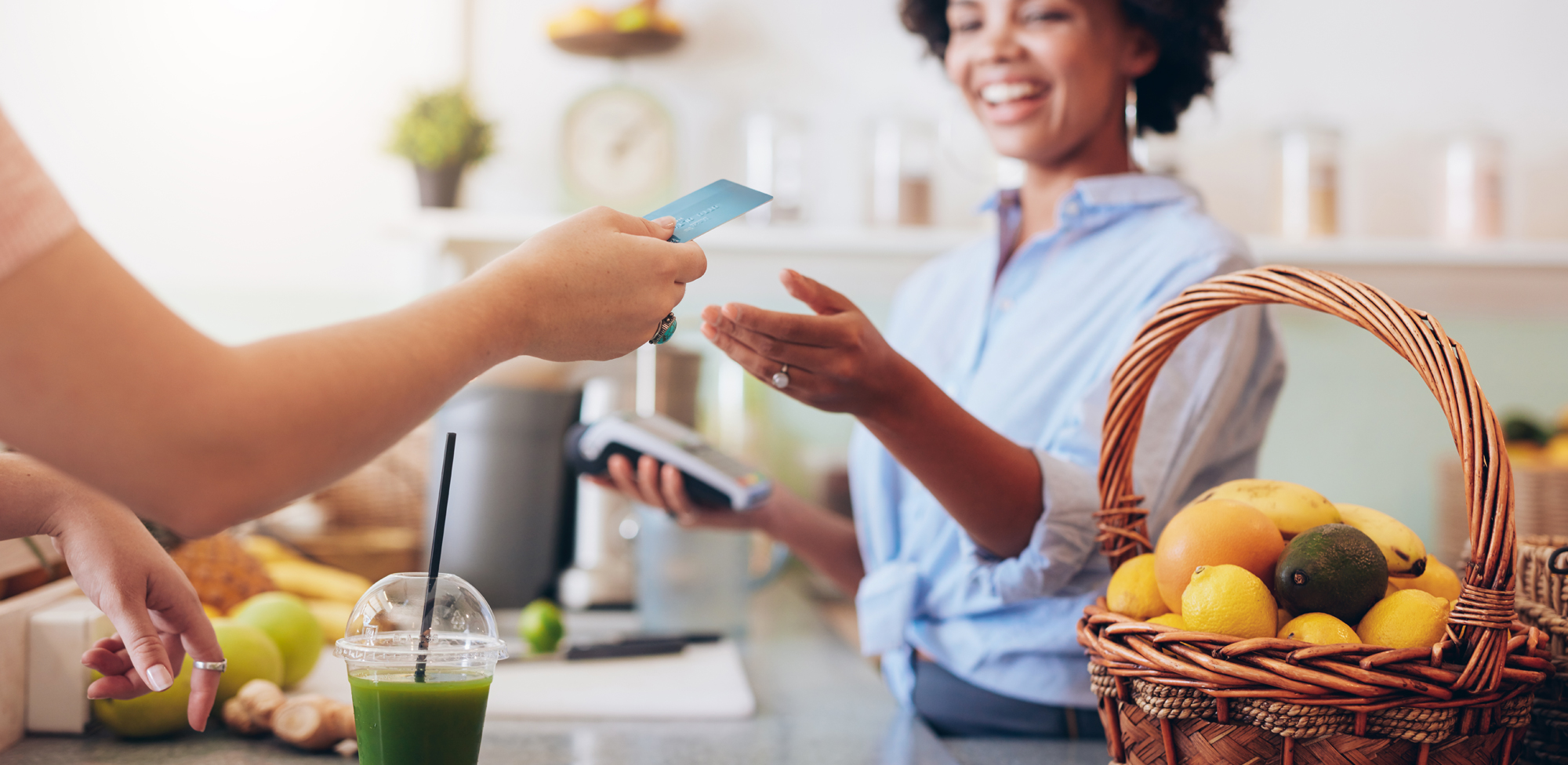 woman buying smoothie with credit card