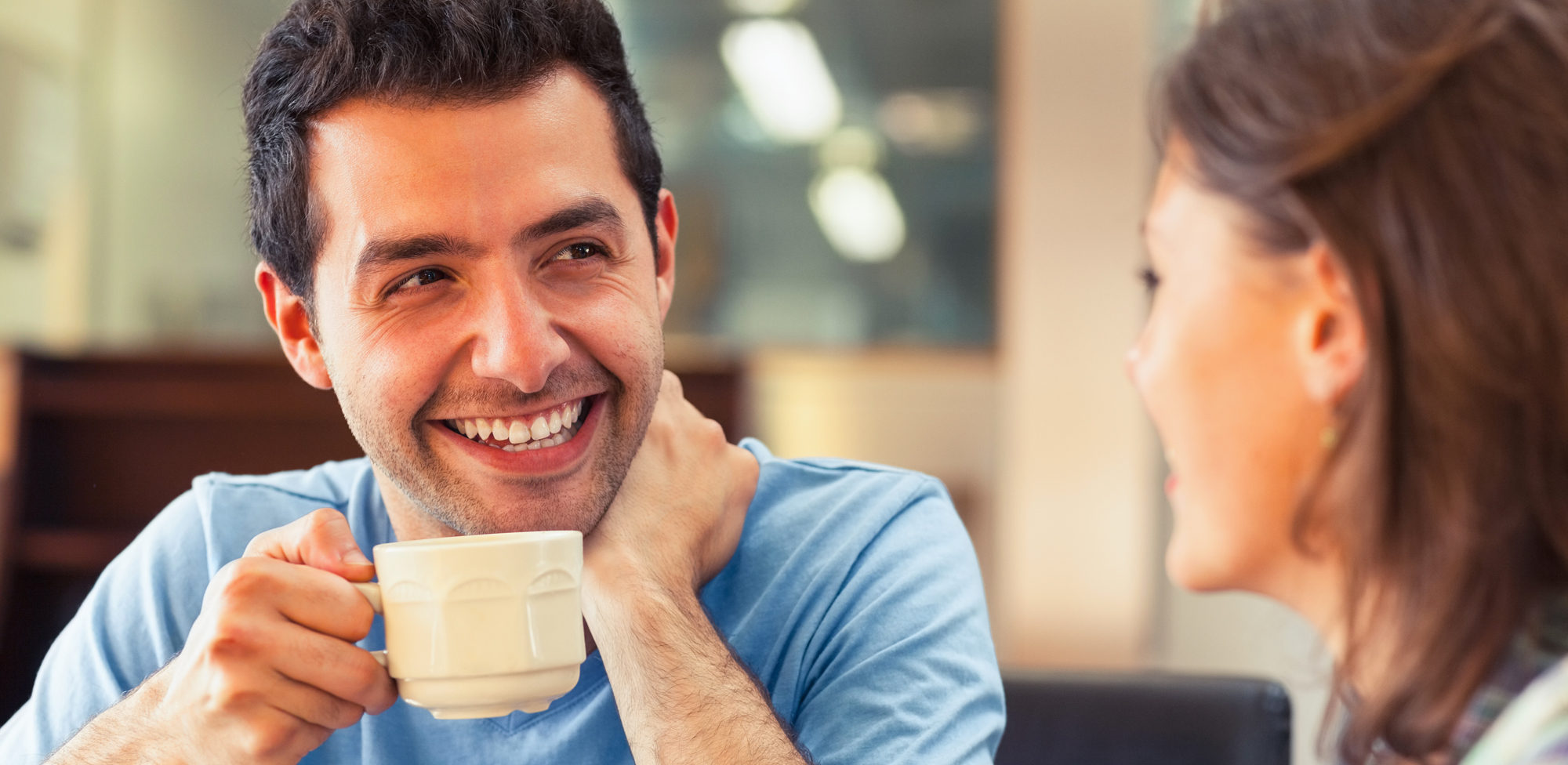 man sitting holding coffee and talking with woman