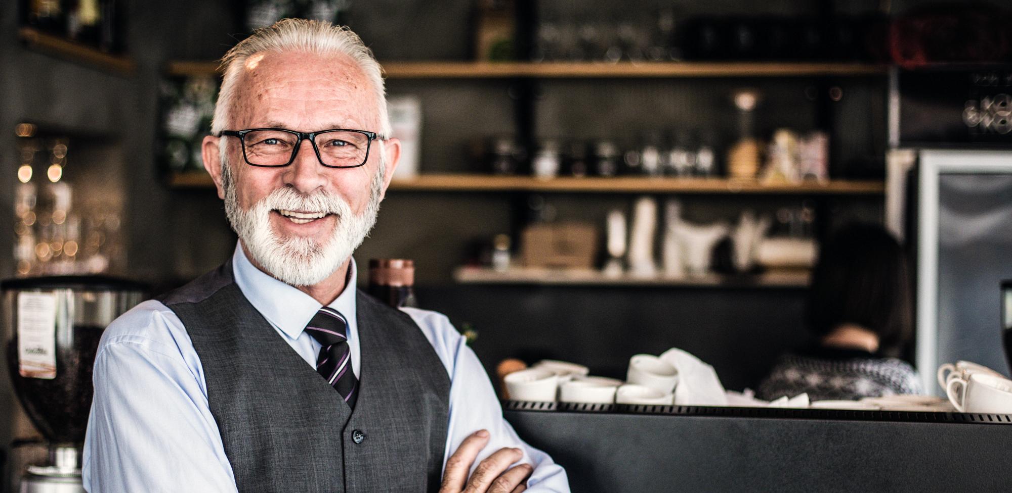 older business man smiling in restaurant