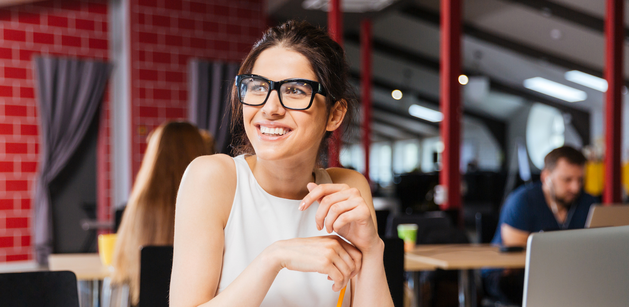 young woman sitting with laptop smiling and looking away