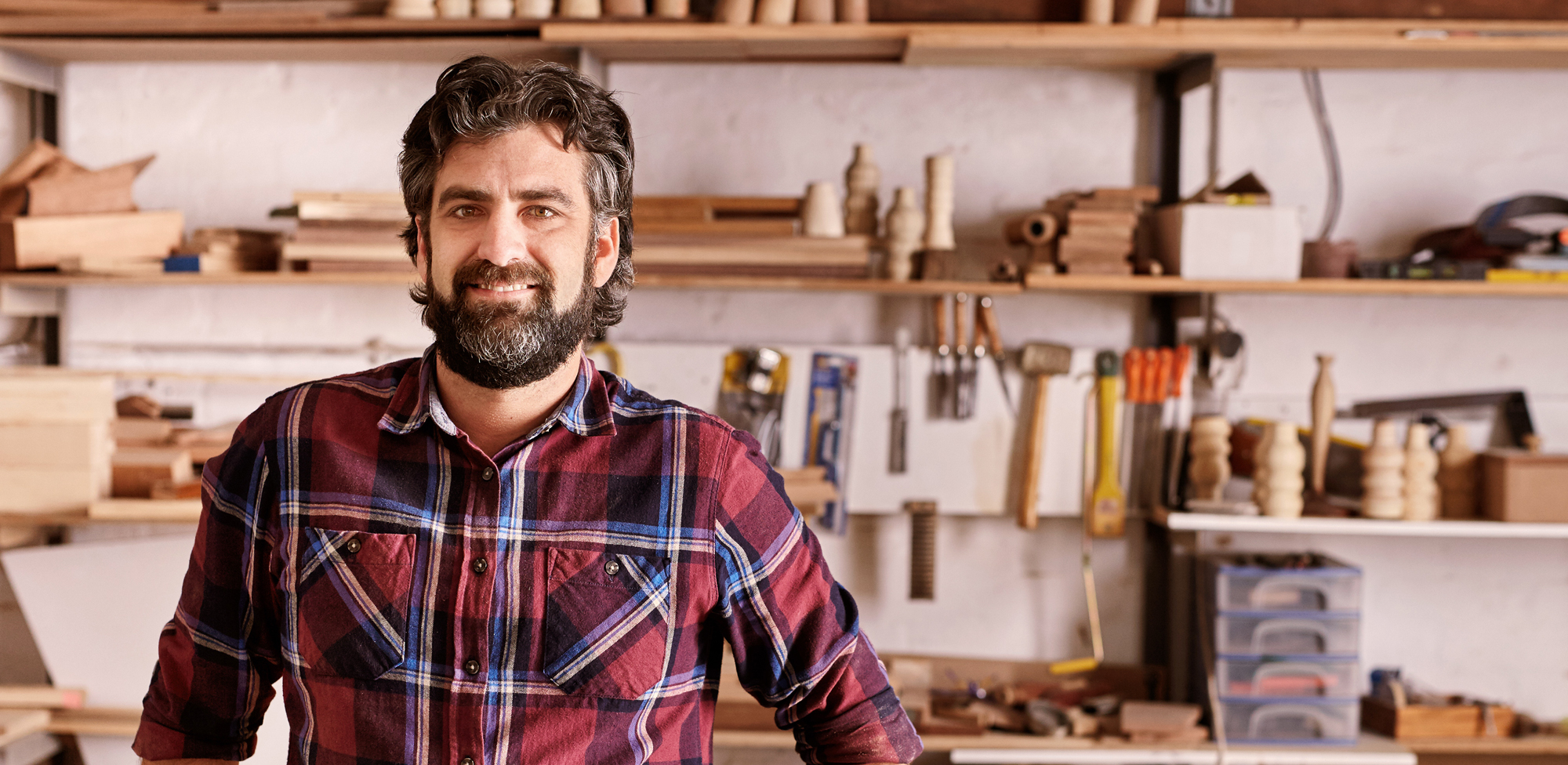 man smiling and standing in front of workshop tool wall