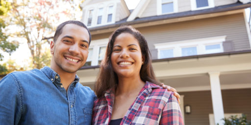 young couple smiling in front of house