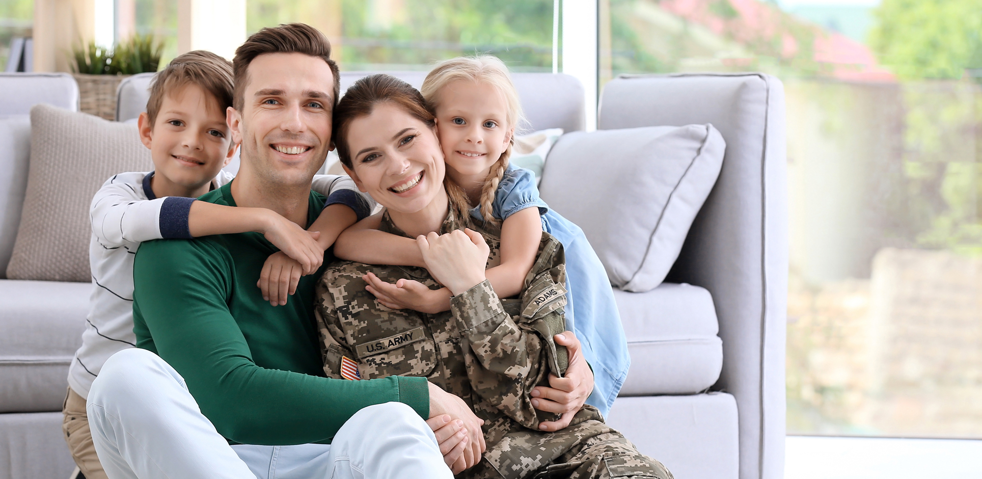 young parents with two kids sitting in front of couch smiling