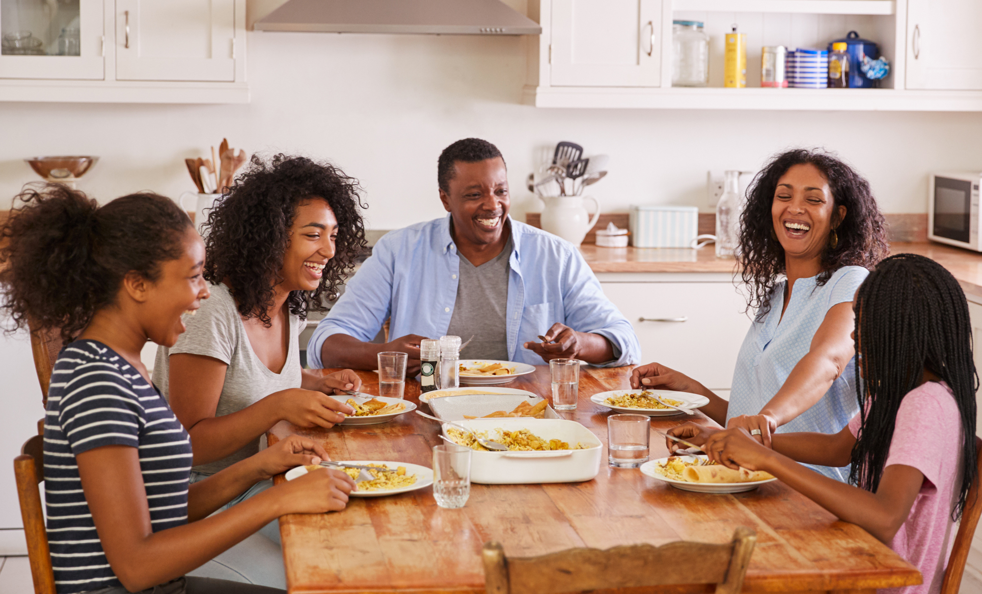 a laughing family eating dinner around a wooden table