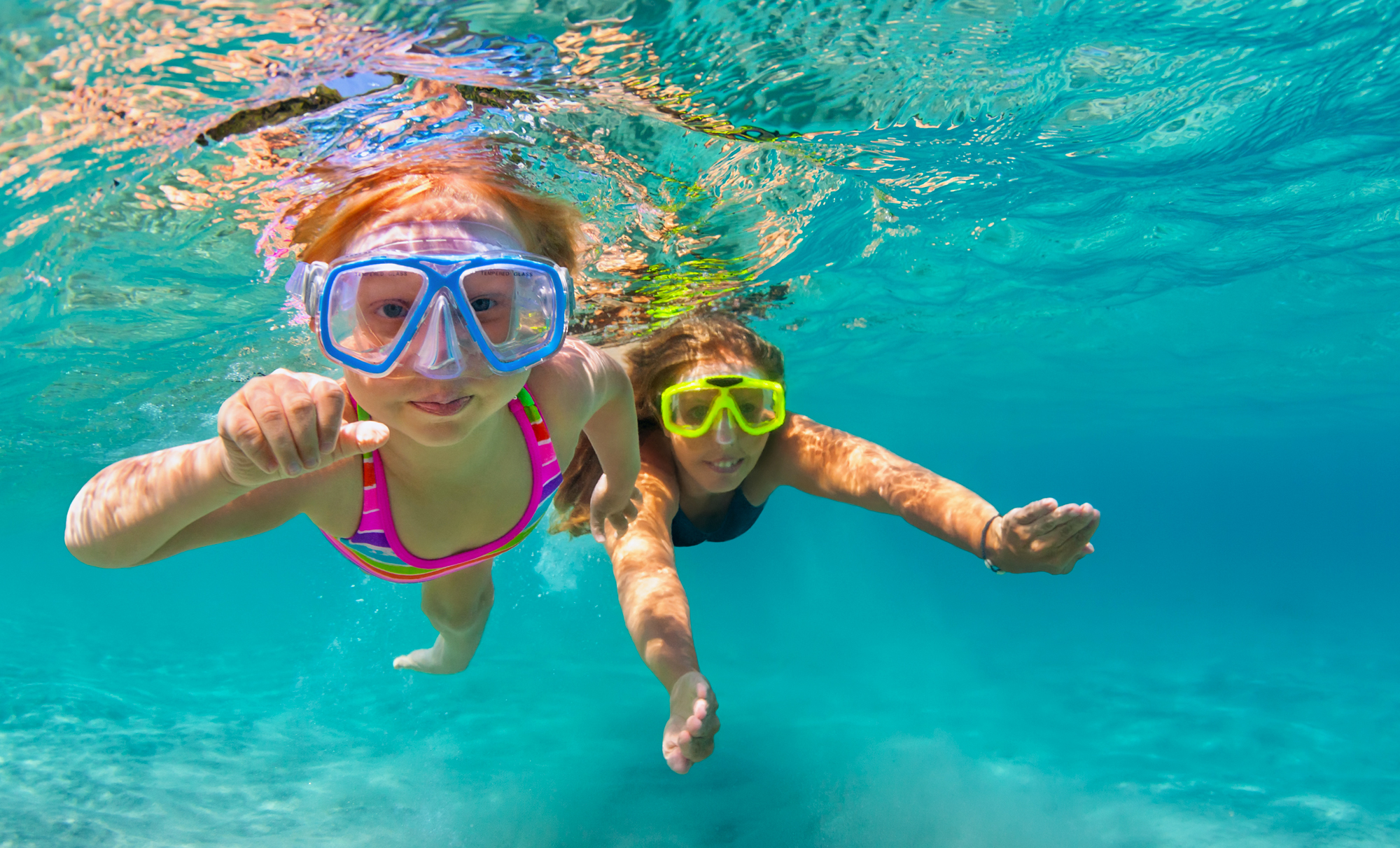 a mom and a daughter with goggles on swimming underwater