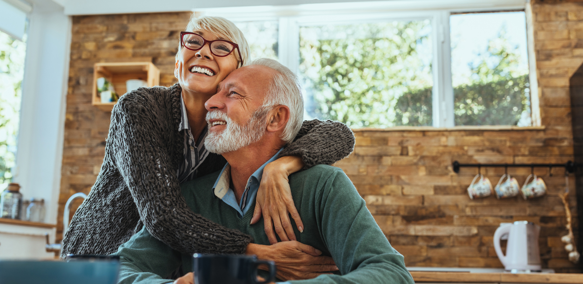 an older man is sitting while an older woman is hugging him, both smiling