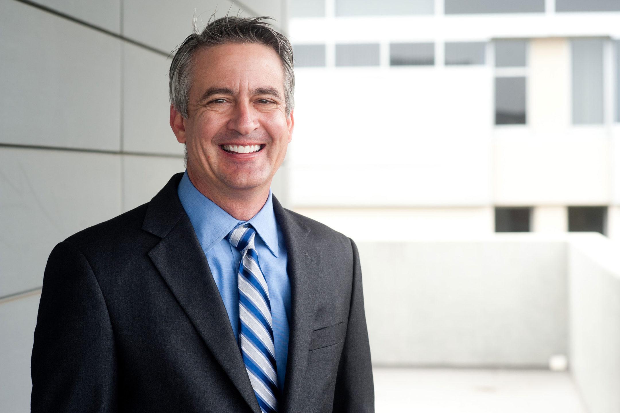 older man smiling in a suit
