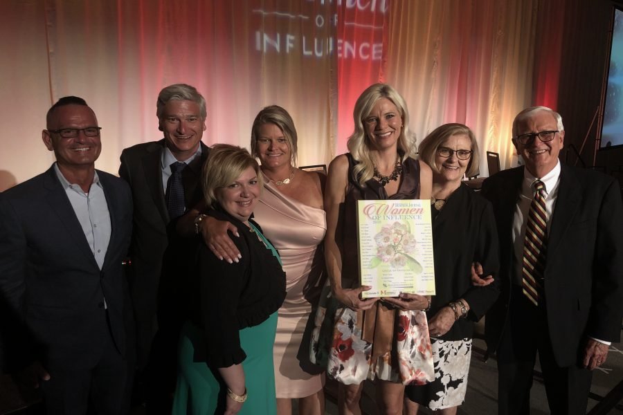 Photo of Liz Dellinger receiving Women of Influence Award with family