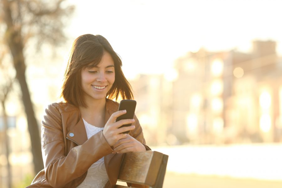 Photo of Happy girl using a smart phone in a city park