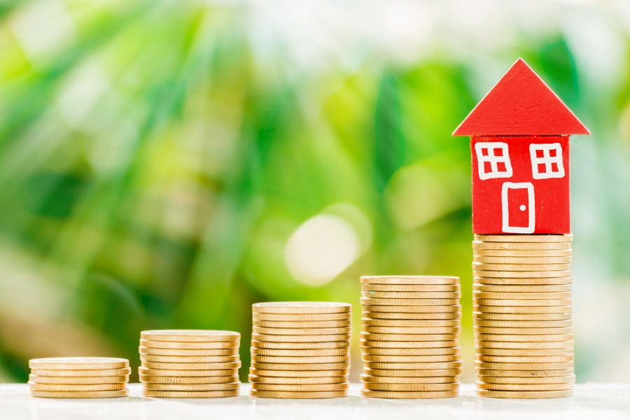 Red home model put on golden coins with fresh green nature