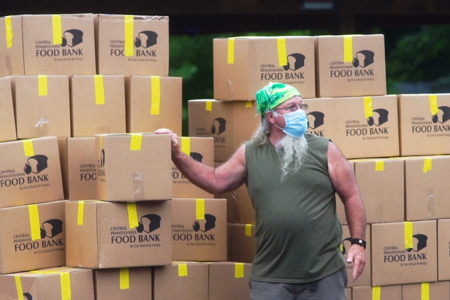 Photo of man in front of Central PA Food Bank boxes to be distributed