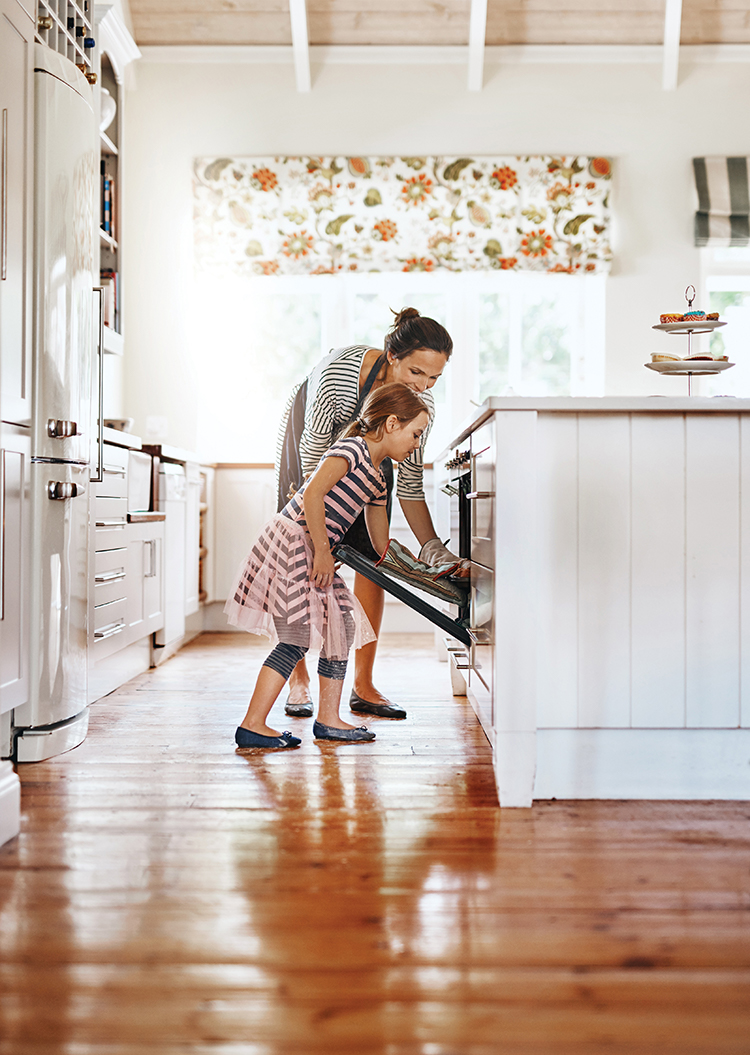 Mother and young daughter in kitchen placing something in the oven