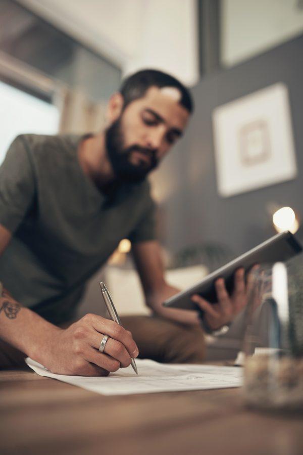 photo of man looking at tablet